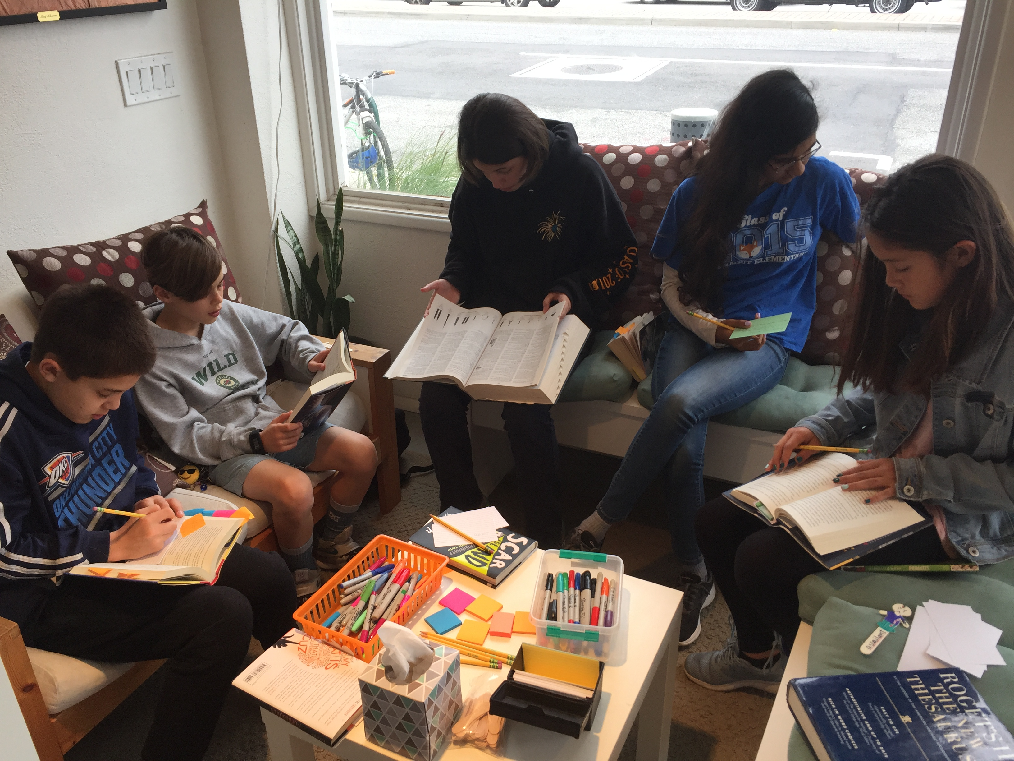 Picture of kids engaged in reading around a table at a Next Generation Leaders summer workshop.